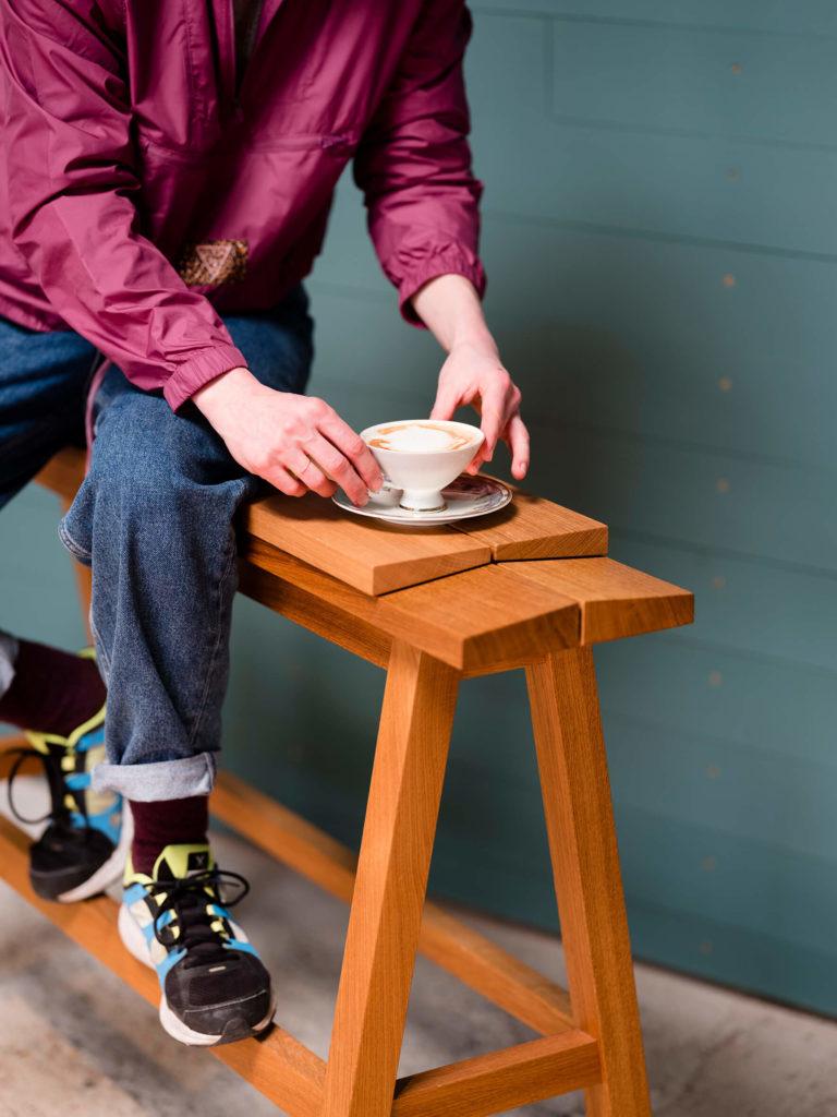 Eine Frau hält eine Tasse mit frischem Kaffee im Barbereich von Ruths Berlin