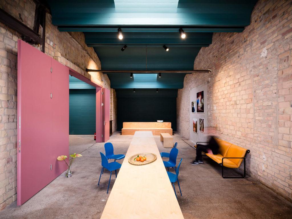 Großer Meetingraum mit langem Tisch, Sitzgelegenheiten und Tribüne